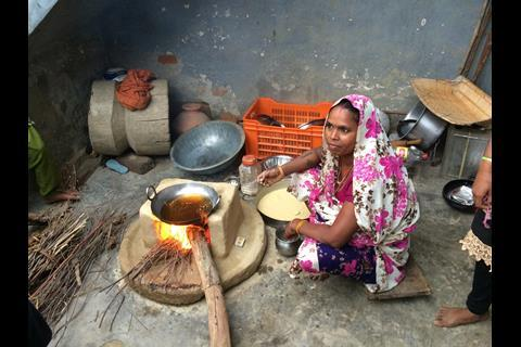 An image of a woman cooking with biomass on an earth stove
